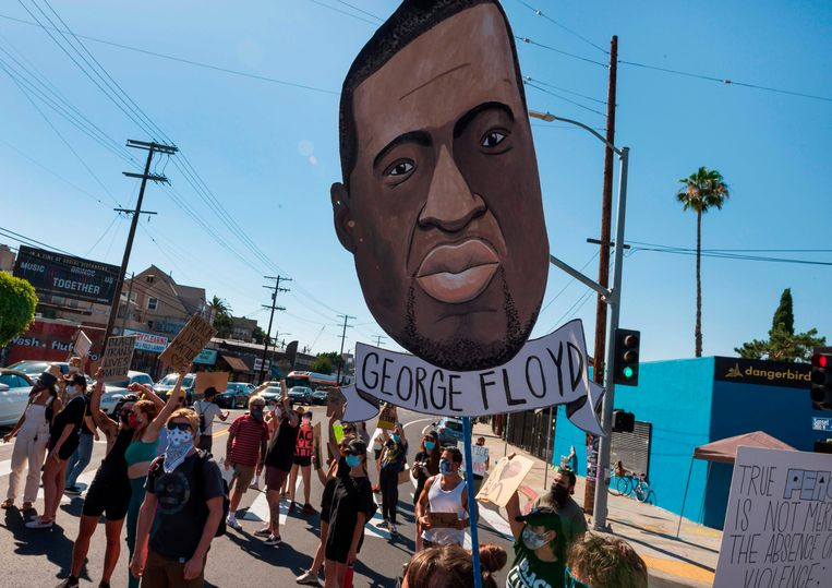 Demonstranten houden een afbeelding van George Floyd omhoog tijdens een protest tegen politiegeweld in Los Angeles.  Beeld AFP