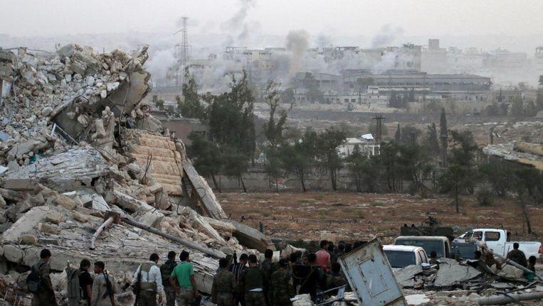 Syrische troepen bij het kapot geschoten Kindi ziekenhuis. Op de achtergrond rookpluimen boven Aleppo. Beeld afp