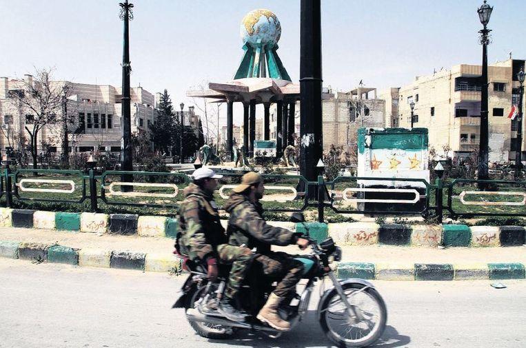 Syrische militairen rijden een rondje op het centrale plein van Jabroed na de inname van de stad. Beeld ap