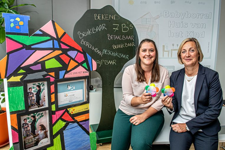 Coördinator Stephanie Rosseel en trotse meter en voorzitter Ann Van Essche delen doopsuikers uit op de babyborrel van het Huis van het Kind.