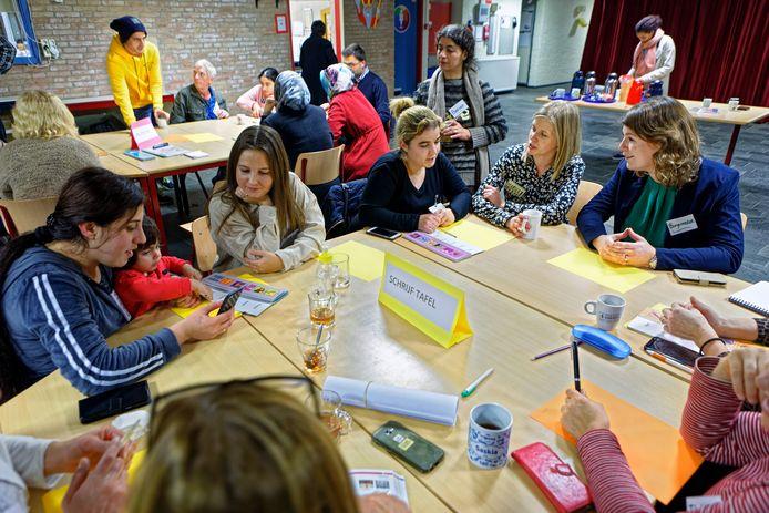Burgemeester Joyce Vermue van Zundert (rechts) bezoekt het Taalcafé in de Annaschool in Zundert.