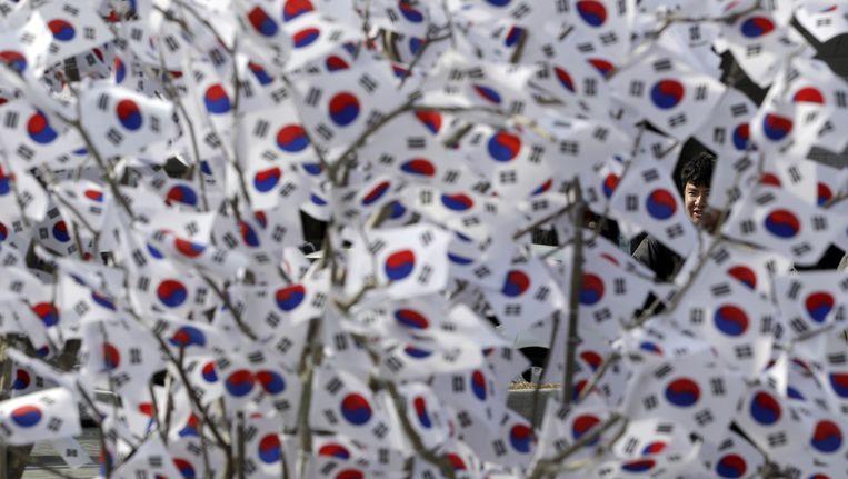 Een man kijkt naar Zuid-Koreaans vlaggetjes tijdens die alvast zijn opgehangen voor de feestdag op 1 maart wanneer de opstand van Zuid-Korea tegen de Japanse koloniale overheersing in 1919 wordt gevierd. Beeld ap
