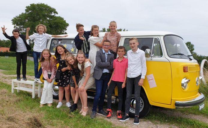 Leerlingen van groep 8 van de basisschool in Maren-Kessel, voor het busje waarmee ze een ereronde door het dorp maakten.