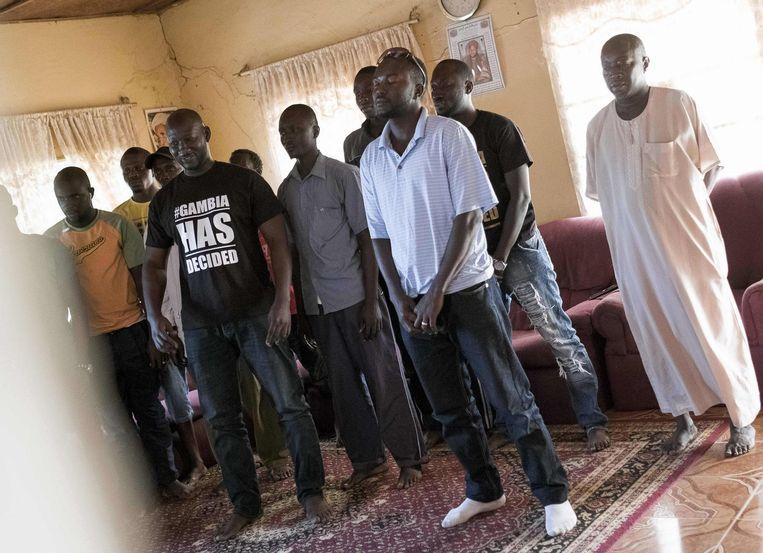 Een groep Gambiaanse mannen kijkt naar de inauguratie van president Barrow op televisie. Beeld null