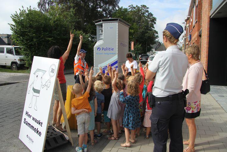 Aandachtige kinderen luisteren naar de uitleg van inspecteur Johan Rommelaere over superflitser Sammeke.