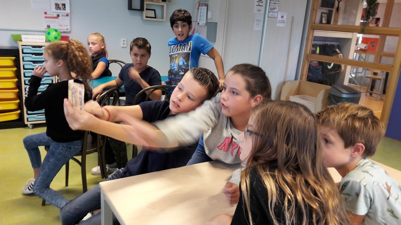 Leerlingen van de Boschuil in Eindhoven controleren een bankbiljet op echtheid tijdens les van minister Wopke Hoekstra.
