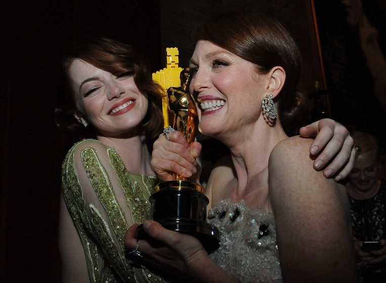 Julianne Moore, die de Oscar won voor Beste Actrice, wordt geknuffeld door collega s Emma Stone, die haar nominatie voor beste vrouwelijke bijrol niet verzilverd zag worden. Beeld afp