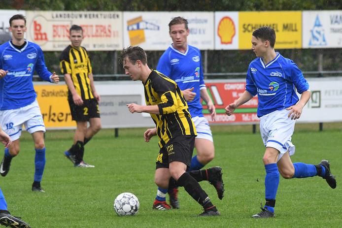Juliana-middenvelder Stan Peters (r) in achtervolging in de derby tegen SES.