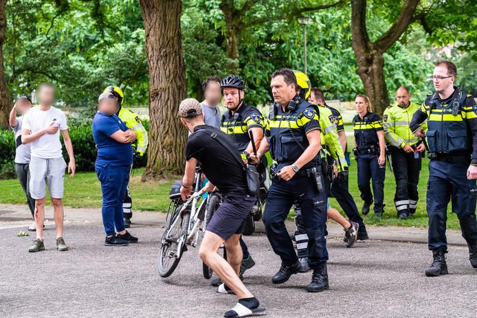 Een jongere wordt weggestuurd door een agent met wapenstok.