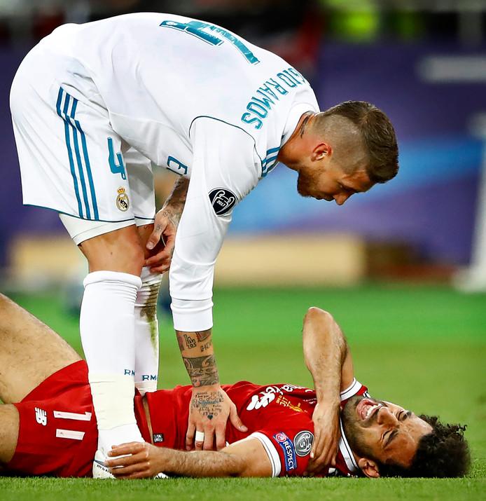 Sergio Ramos die zich bekommerd om Mohamed Salah die verkeerd op zijn arm terechtkomt en uitvalt.