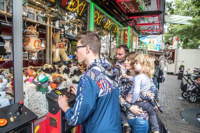 Joey beproeft z'n geluk bij de grijpautomaten, terwijl zijn ouders en broertje Joey toekijken. Foto Frans Paalman