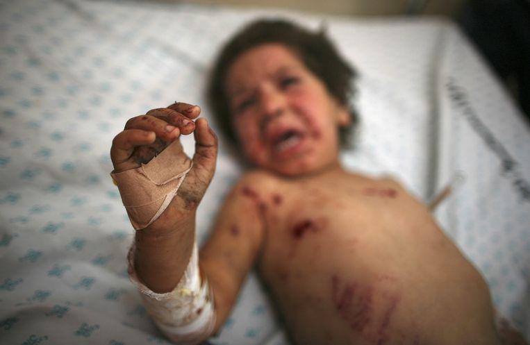 Een Palestijns meisje van vier wordt behandeld nadat ze gewond is geraakt bij een Israëlische luchtaanval. Beeld reuters