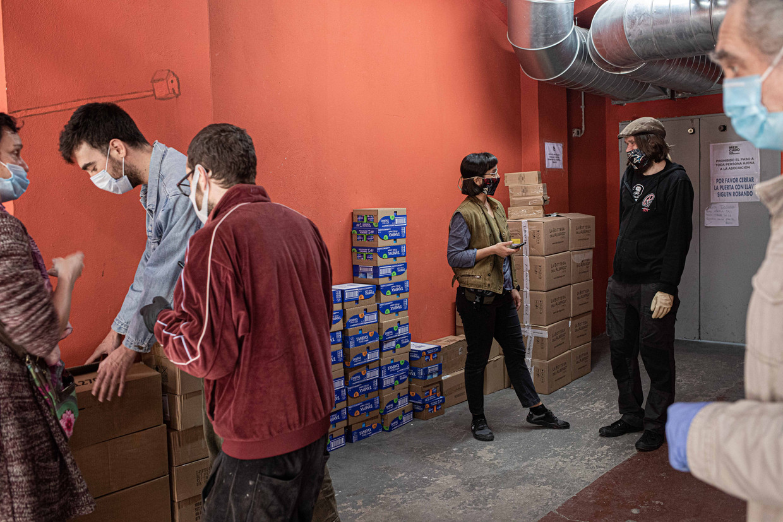 Vrijwilligers van de buurthulp in een wijk in Madrid buigen zich over de verdeling van de binnengekomen goederen voor kwetsbare inwoners.   Beeld Cesar Dezfuli
