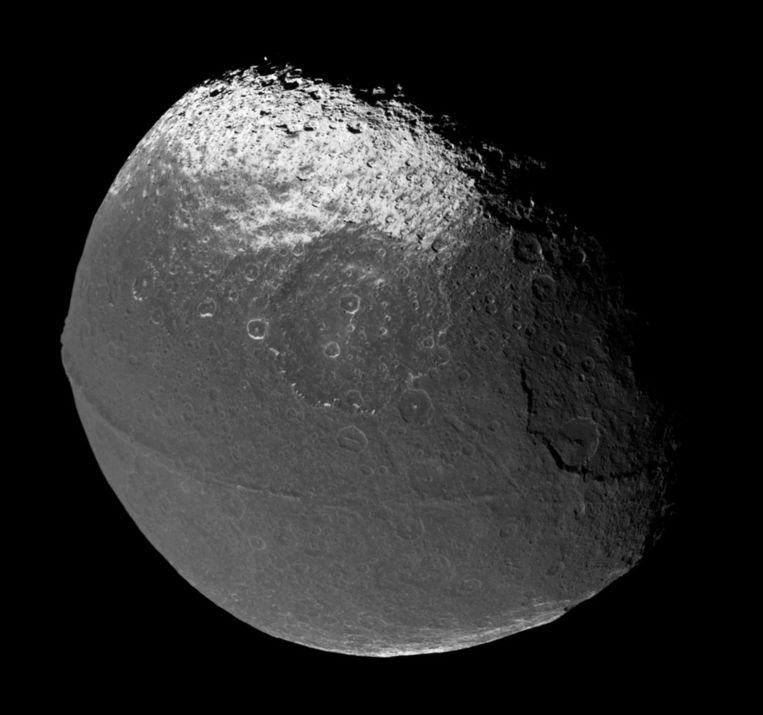 Op deze foto van Iapetus van Nasa is de 'kam' rond de evenaar goed te zien. Hierdoor krijgt de maan de vorm van een walnoot. Beeld Nasa