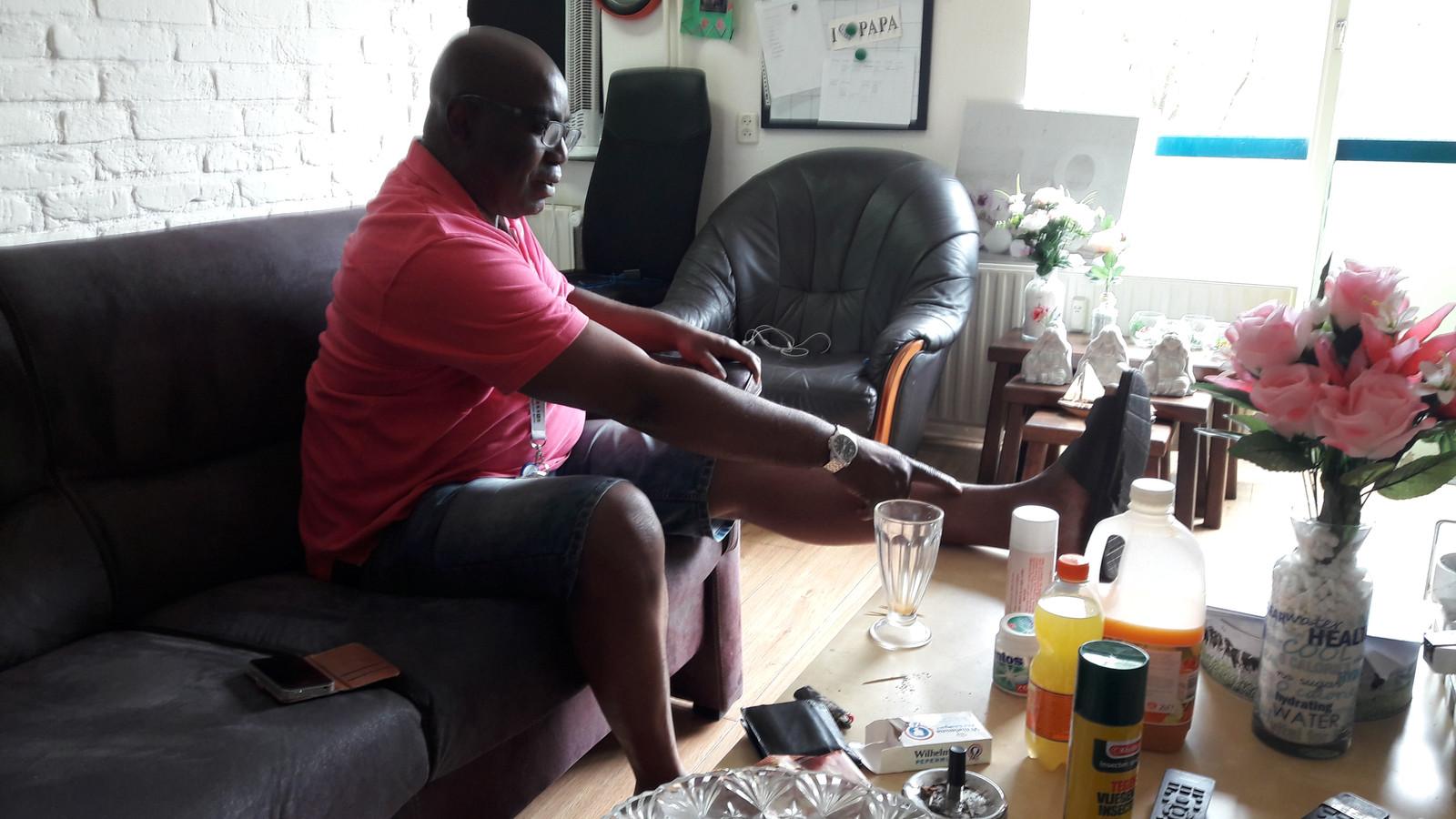 Wilfred Mbadugha wijst de plek aan waar hij de meeste pijn heeft.