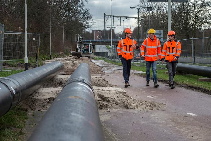 Buizen voor de uitbreiding van de stadsverwarming in Breda liggen klaar op de Lunetstraat om ingegraven te worden. Links operationeel directeur Tom Emons van Ennatuurlijk, in het midden de projectleider van Heijmans, rechts Hans Lazeroms van Ennatuurlijk, verantwoordelijk voor het netwerk in Breda.