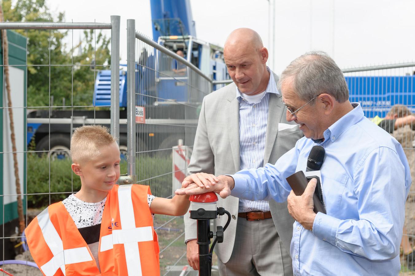 Wethouder Raemaekers en Rick geven startsein voor plaatsing glasvezelcentrale in Wanroij.