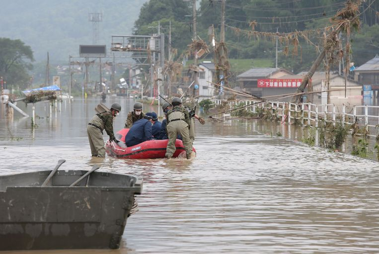 Reddingswerkers zijn ingezet om Japanners die vastzitten als gevolg van het noodweer te evacueren.  Beeld AFP