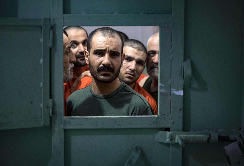 Mannen die ervan verdacht worden banden te hebben met IS kijken naar buiten door het luik van hun cel.   Beeld AFP