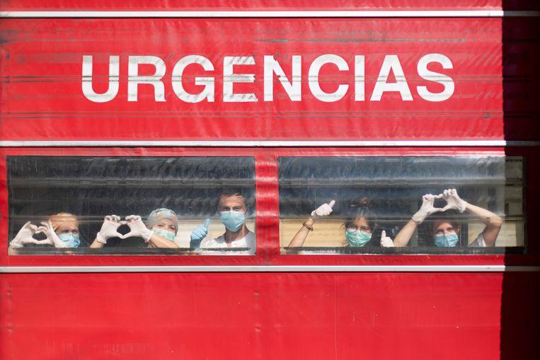 Terwijl medisch personeel zich voorbereidt op nieuwe patiënten, gebaren ze berichten van hoop. Beeld Getty Images