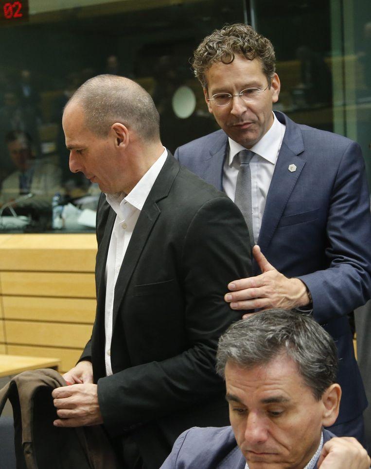 Eurogroepvoorzitter Dijsselbloem dirigeert de Griekse minister van Financiën Varoufakis naar zijn stoel. Beeld epa