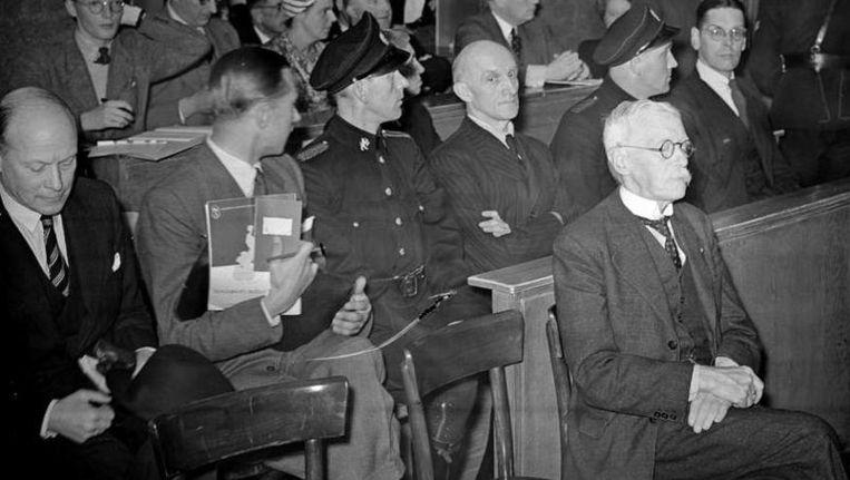 Dirk de Geer wacht in mei 1947 zijn strafzaak af. Hij zit voor de getuigenbank met daarin - tussen parketwachten - de hooggeplaatste NSB'ers Ernst Voorhoeve (links) en Toby Goedewaagen. Beeld ANP