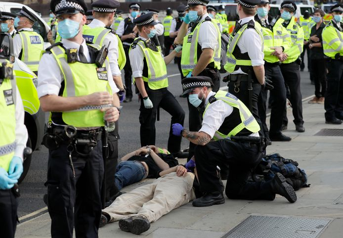Agenten met mondkapjes houden twee demonstranten aan in het centrum van Londen.