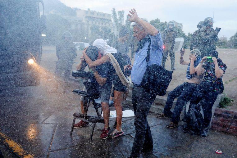 Mensen beschermen zich tegen een waterkanon dat de politie heeft ingezet.