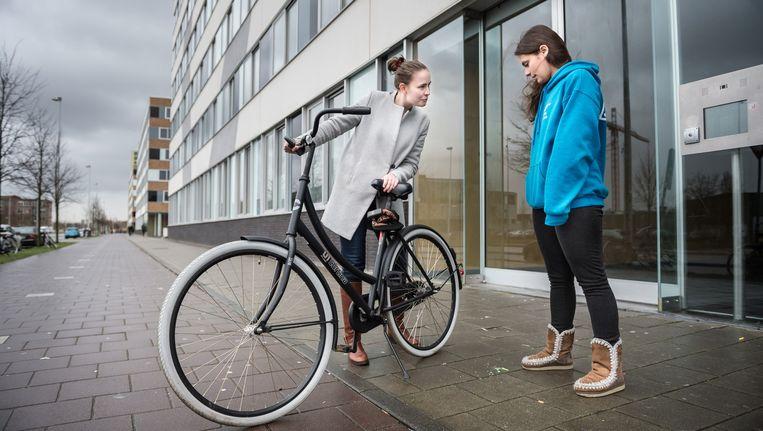 Alesi Enriquez (rechts) verhuurt haar fiets aan medestudent Lia Sinnige Beeld Mats van Soolingen