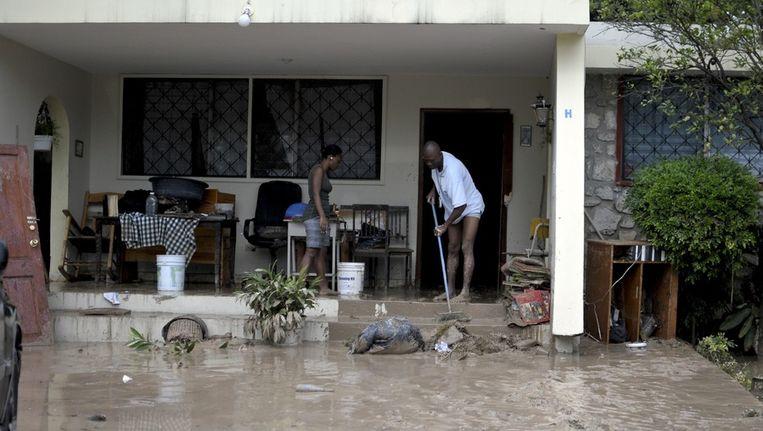 Inwoners van Port-au-Prince vegen de modder uit hun gisteren door de storm ondergelopen huis. Beeld null