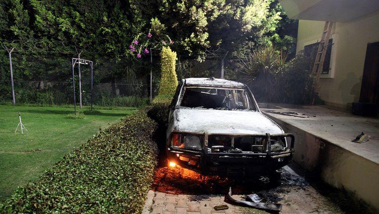 Een uitgebrande auto bij het Amerikaanse consulaat in Benghazi. Beeld AFP