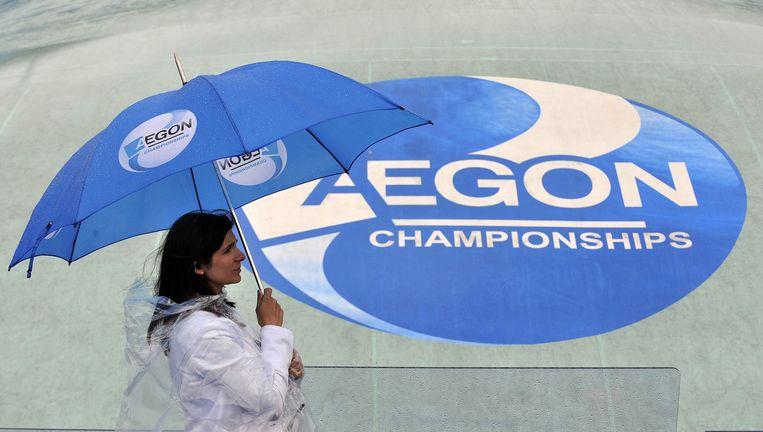 Een steward met een paraplu van sponsor Aegon bij het tennistoernooi van Queen's in Londen in 2011. Beeld EPA