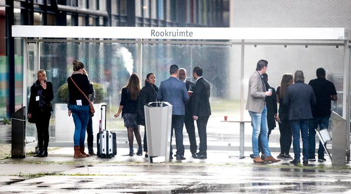 Bezoekers aan de vakantiebeurs roken een sigaret in een rookruimte in de Utrechtse Jaarbeurs.