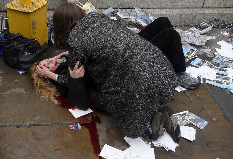 Een voorbijganger ontfermt zich over een slachtoffer na de aanslag nabij het Britse parlement Beeld Toby Melville/Reuters