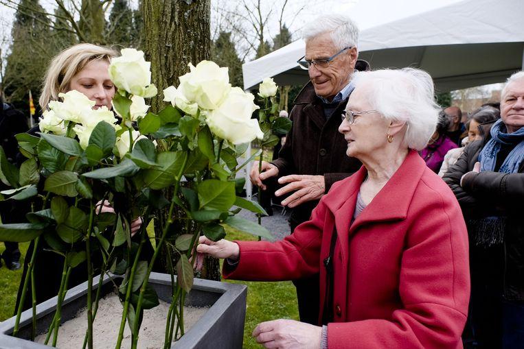 Een vrouw plant een witte roos voor de slachtoffers van de oorlogsbombardementen.