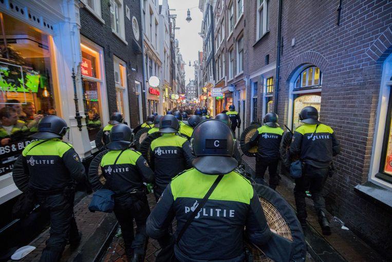 Politieagenten van de ME op de Amsterdamse Wallen waar Engelse voetbalfans voor onrust zorgen. De supporters waren in de stad voor het oefenduel tussen Nederland en Engeland in de ArenA. Beeld ANP