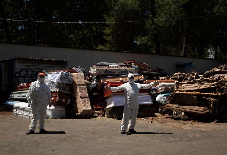 Een medewerker van een crematorium in Mexico-Stad begeleidt een lijkwagen naar binnen. De overledene is vermoedelijk gestorven aan covid-19. Beeld AP