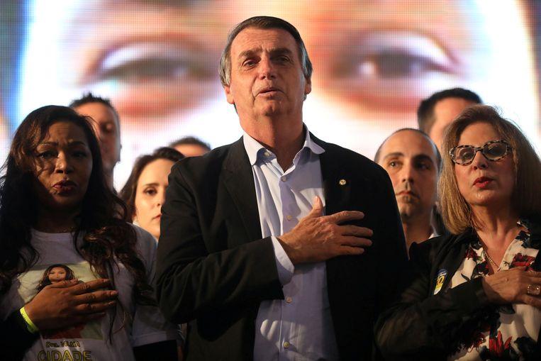 Presidentskandidaat Jair Bolsonaro luistert naar het volkslied. Beeld REUTERS