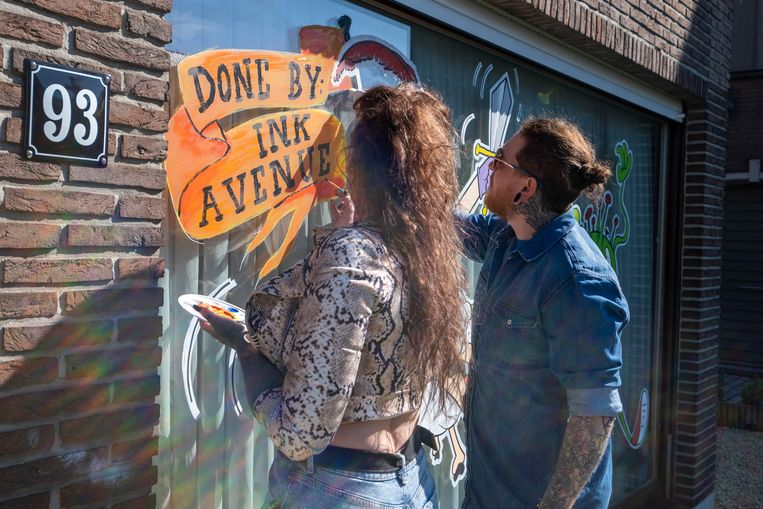 Tattoo-artiesten Melni Sikorski en Yannick Van Ginneken beschilderen ramen in coronathema.