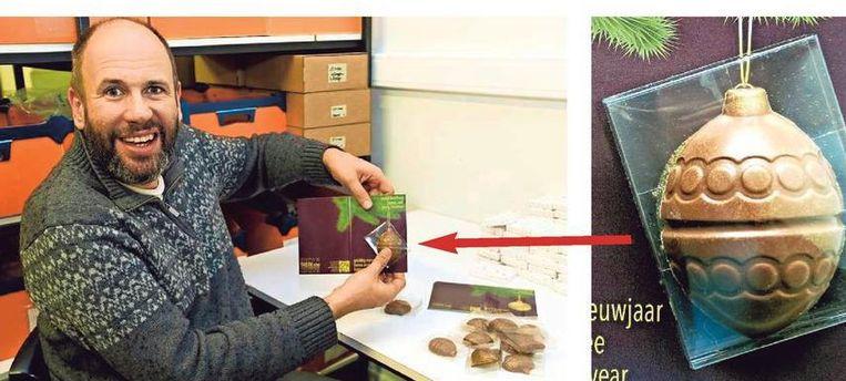 Werknemer Sven toont een kerstkaart met een kerstbal (rechts) in chocolade.