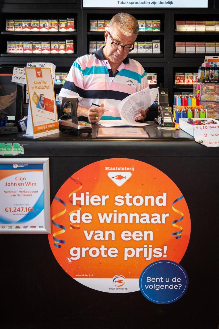 Wim van Vuure achter de toonbank van zijn Cigo, dat dit jaar nummer één verkooppunt van de Nederlandse loterij werd Beeld Dingena Mol