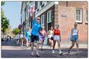 Groepen van maximaal 20 studenten lopen door de stad.