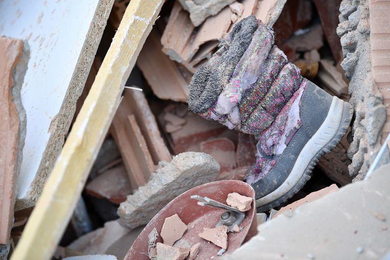 Een kinderlaarsje in het puin van de ingestorte woning.