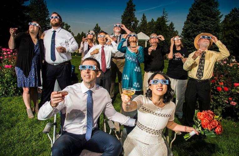 Bruid en bruidegom Nathan Mauger en Connie Young toosten in Washington met hun familie op de zonsverduistering. Beeld AP