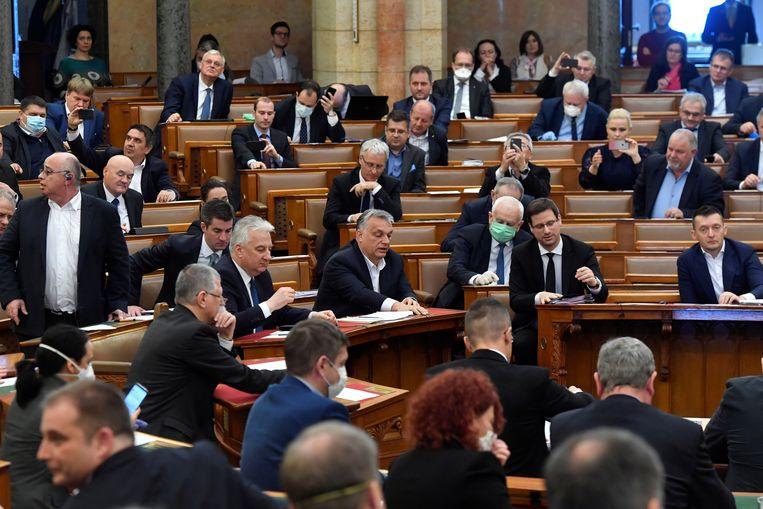 Met de maandag in het parlement aangenomen wet kan Viktor Orbán (midden) grotendeels per decreet regeren.  Beeld Reuters