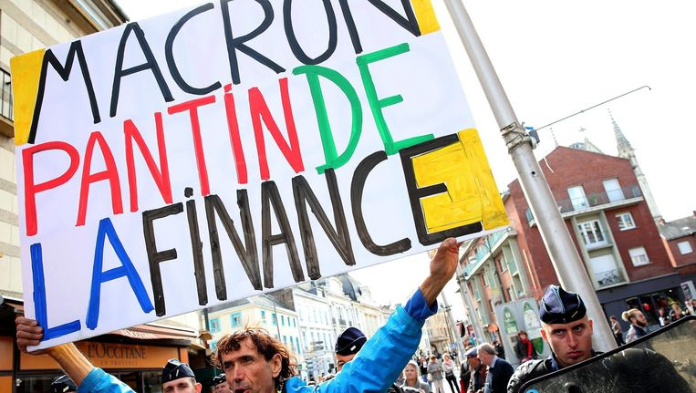 Een demonstrant met een bord met daarop 'Macron, marionet van het geld.' Beeld afp