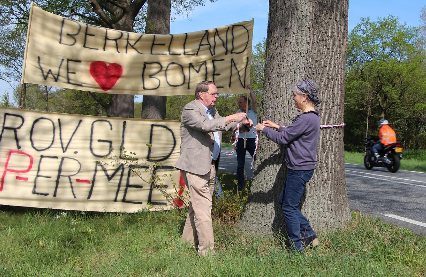 Jaap Cannegieter en Petra Sips hangen een koord om een van de bedreigde eiken langs de N319.