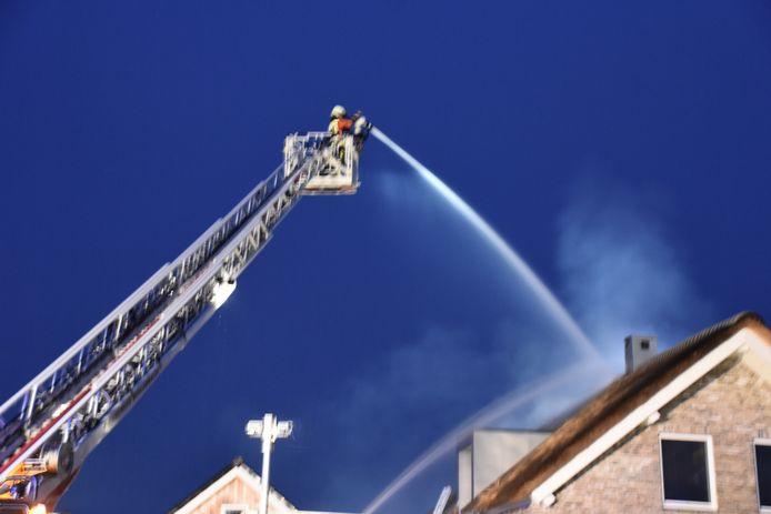Vanaf een ladderwagen blust de brandweer het vuur in het rieten dak aan de Henegouwernesse