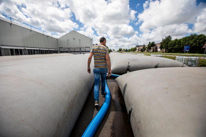 Gierzakken gevuld met 2 miljoen liter water liggen op het terrein van Sion verspreid. Ron Moor van Sion geeft uitleg.