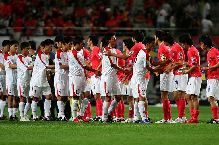 Zuid- en Noord-Koreaanse spelers schudden elkaar de hand tijdens het WK in 2010. Beeld Getty Images